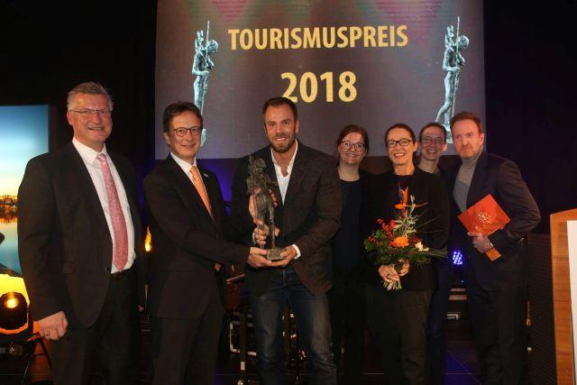 Dominic Boeer (Mitte) nimmt den 9. Tourismuspreis MV für die SOKU Wismar entgegen.